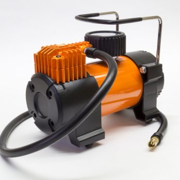 Orange electric compressor for car on light background