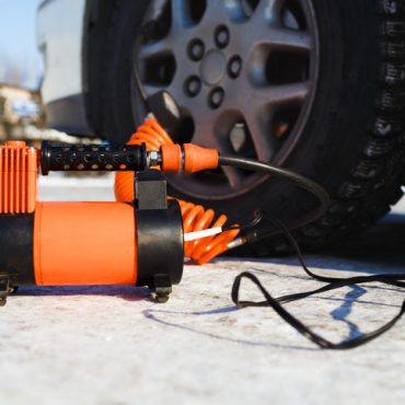 Car air compressor in working position at snow. Winter self-inflating wheels at the car in the field. The orange color, sunny winter day. Automobile tire pressure control.