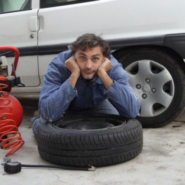 Changing a tire, pensive man and spare wheel